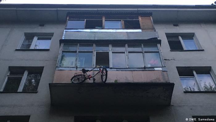 Старый многоквартирный дом, за балкон которого вывешен велосипед