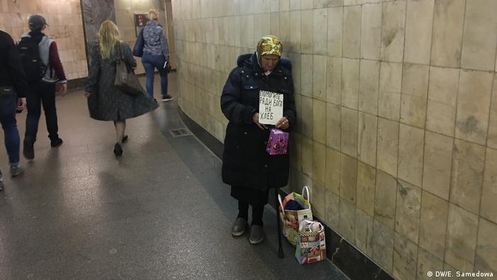 Просящая милостыню в подземном переходе пожилая женщина