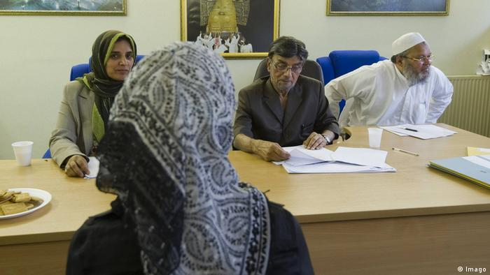 A woman sits in front of a Sharia court