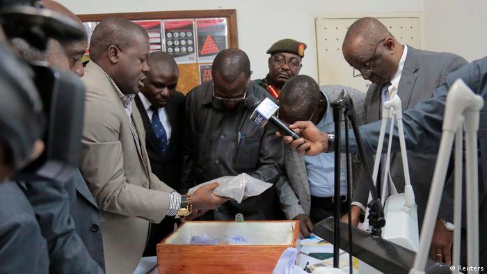 Government officials look at diamonds seized at the airport in Tanzania