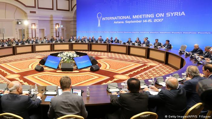 A large hall with a big circular table at which mostly men in suits are sitting. The enormous banner on the blue colored wall read International Meeting on Syria