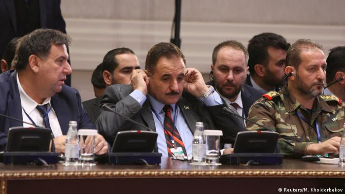 Ahmed Beri, chief of staff of the Free Syrian Army, adjusts his headphones during the latest round of talks in Astana, Kazakhstan.