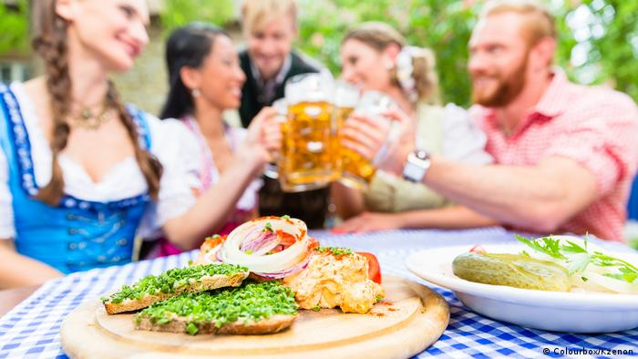 Five friends, women and men, sitting in beer garden clinking glasses having Bavarian appetizers on the table (Colourbox/Kzenon)