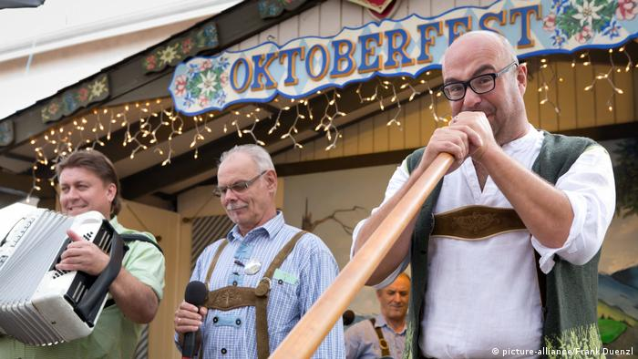 Vor einer Holzhütte mit der Aufschrift Oktoberfest musizieren drei Männer