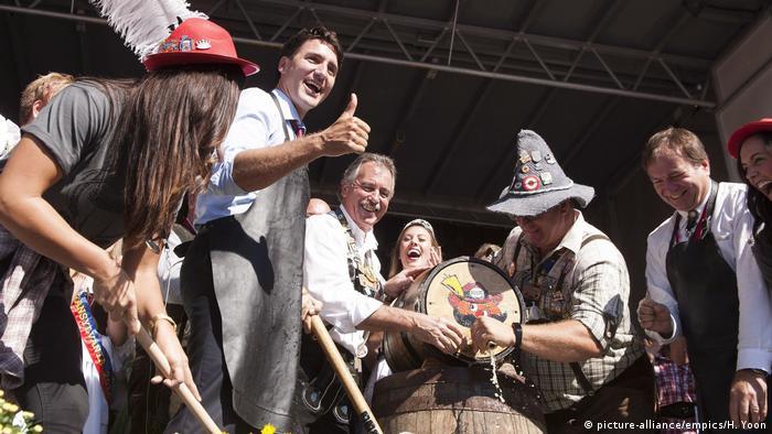Premierminister Justin Trudeau steht mit anderen Leuten neben einem Bierfass, das angeschlagen wird . Er macht das Ziechen Daumen hoch