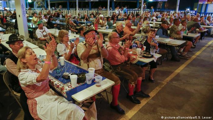 Männer und Frauen in Lederhosen und Dirndln sitzen an langen Tischen und applaudieren