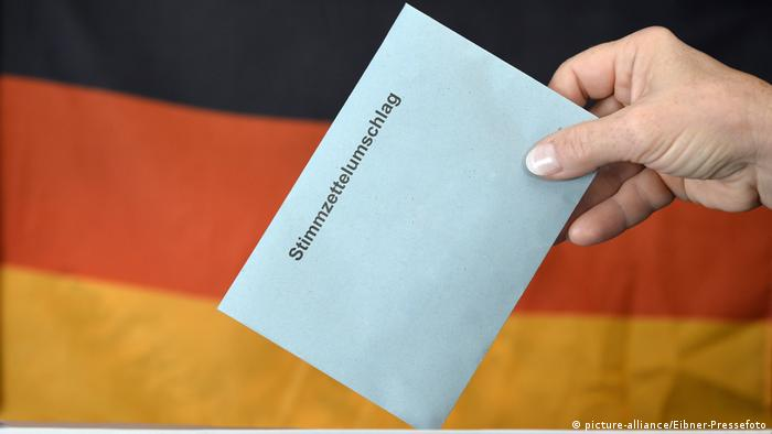A hand holding an election document against the backdrop of the German flag