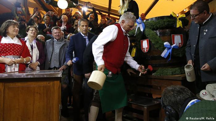 Münchens Oberbürgermeister Dieter Reiter schlagt in Tracht ein Fass an, viele Menschen schauen zu