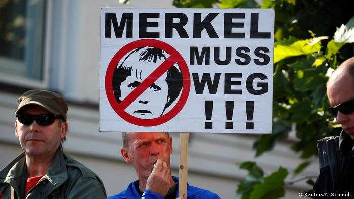 A man holds a sign reading Merkel must go! at a campaign rally