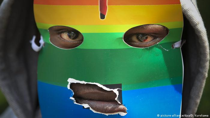 A man with a rainbow-colored mask marches in favor of gay rights in Kenya