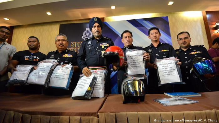Amar Singh and police officers hold up evidence bags in Kuala Lumpur (picture-alliance/Zumapress/C. V. Chung)