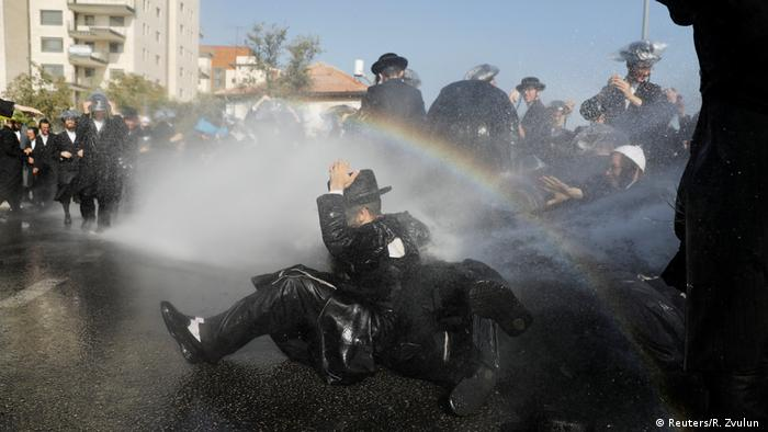 Protester sits down in the street while being sprayed by police water canon (Reuters/R. Zvulun )