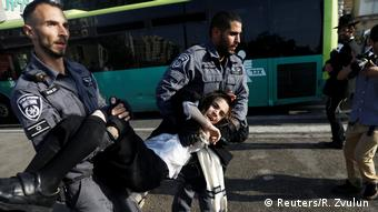Two policeman carry an ultra-Orthodox Jewish youth during the protest in Jerusalem (Reuters/R. Zvulun )
