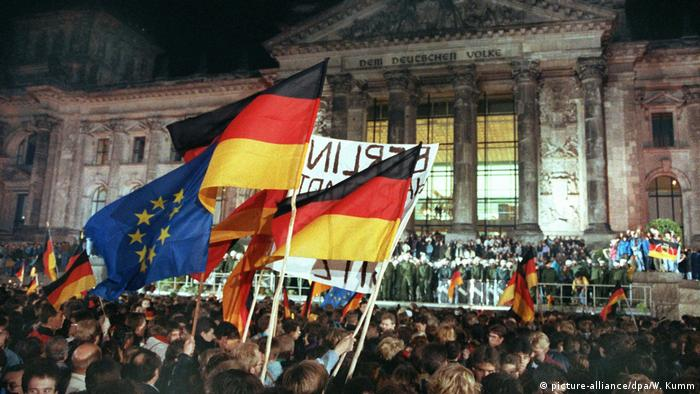 Poeple celebrate German unification in front of the Reichstag in Berlin on October 3, 1990