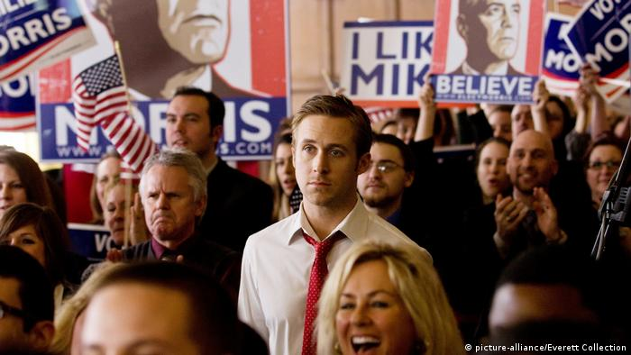 Film still Ryan Gosling, The Ides of March, scene from an election campaign, people cheering and holding flags and posters (picture-alliance/Everett Collection)