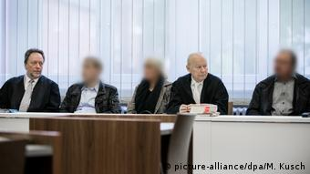Three suspects sit with their lawyers in the courtroom, their faces are blurred