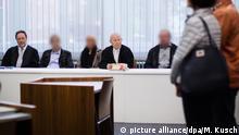 18.9.2017*** Die drei Angeklagten warten am 18.09.2017 in Essen (Nordrhein-Westfalen) im Gerichtssaal neben ihren Anwälten Gerd Küppers (l) und Manfred Gregorius (4.v.l.) auf den Prozessbeginn. Die Angehörigen des Opfers stehen rechts. Es begann der Prozess gegen zwei Männer und eine Frau begonnen, die in einer Bankfiliale einen bewusstlosen Rentner ignoriert haben sollen.Sie sind vor dem Amtsgericht wegen unterlassener Hilfeleistung angeklagt. (ACHTUNG: Die Angeklagten sind auf Anforderung des Gerichts zum Schutz ihrer Persönlichkeitsrechte unkenntlich gemacht worden.) Foto: Marcel Kusch/dpa +++(c) dpa - Bildfunk+++ | Verwendung weltweit