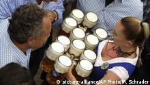 A waitress carries 12 beer mugs during Octoberfest in Munich.