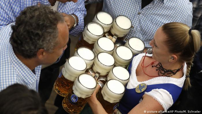 Waitress holding mugs of beer at Oktoberfest 2017 (picture-alliance/AP Photo/M. Schrader)