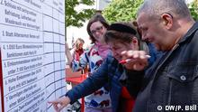 Election campaign event in Cologne: people pointing at issues written on a board (DW/P. Böll)