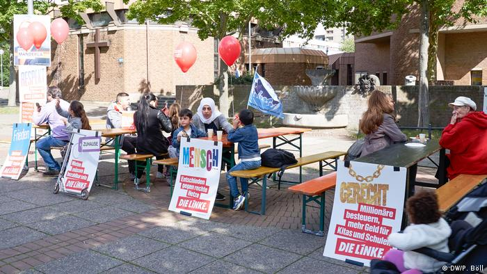 People sitting at tables outside decorated with signs and balloons at an event of the Left Party.