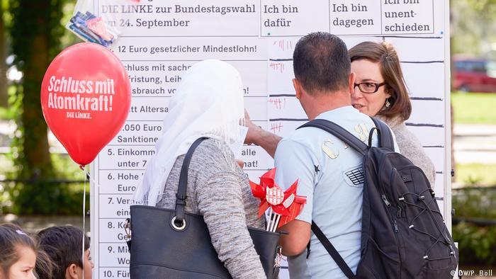 Bürger vor einem Informationsplakat der Partei Die Linke in Köln (Foto: DW/P. Böll)