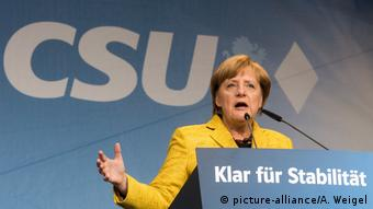 Chancellor Merkel stands in front of a CSU campaign poster in Passau (picture-alliance/A. Weigel)