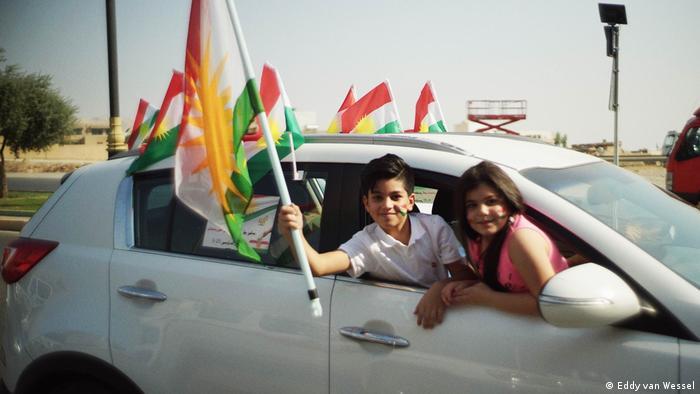 Kinder halten eine Flagge aus einem fahrenden Auto, aufgenommen in Erbil (Eddy van Wessel)