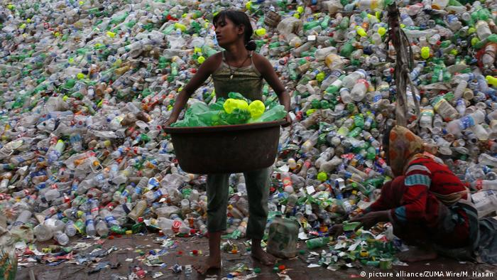 Children in front of a huge pile of plastic bottles
