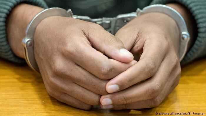 Руки темнокожего человека в наручниках