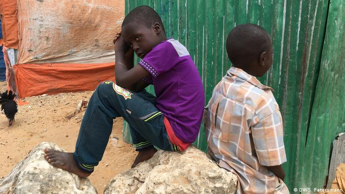 Two children sit back to back on a rock (DW/S. Petersmann)