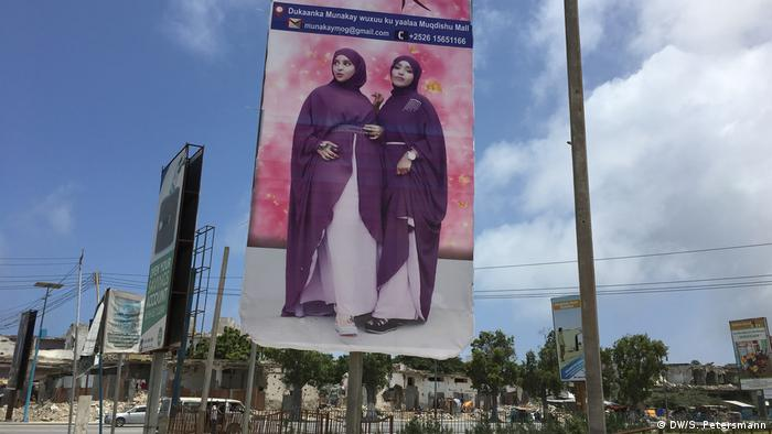 An advert shows two women posing in matching purple robes (DW/S. Petersmann)