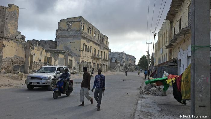 Two men walk;a motorbike-rider and a car drive through a street between ruined buildings (DW/S. Petersmann)