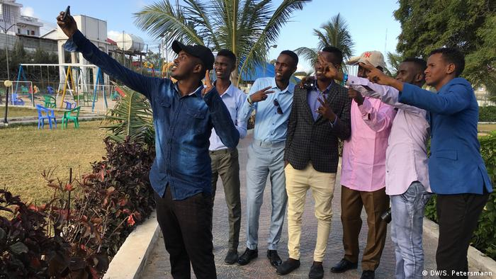 A group of young men take a 'selfie' in Peace Park (DW/S. Petersmann)