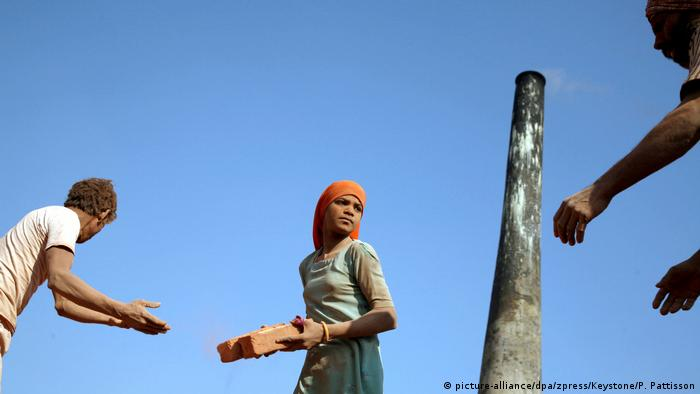 Children carry bricks in India