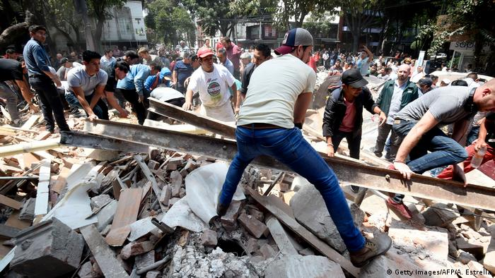 People remove debris of a building which collapsed after a quake rattled Mexico City (Getty Images/AFP/A. Estrella)