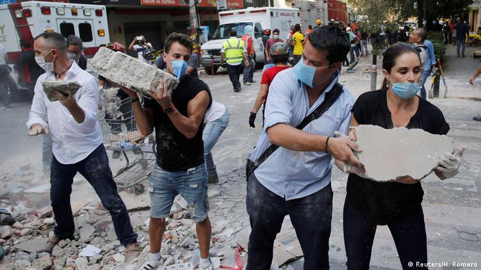 люди помогают при разюоре завалов в Мехико