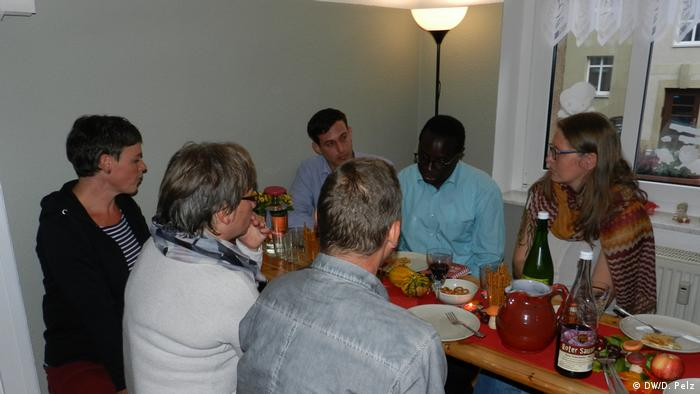 Karamba Diaby and a group of people sitting around a wodden table with plates, whine and food