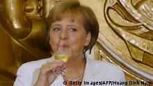 Visiting German Chancellor Angela Merkel (L) and her Vietnamese counterpart Nguyen Tan Dung drink champagne after a signing ceremony at the government guest house in Hanoi on October 11, 2011. Merkel began her two-day official visit to Vietnam aimed at boosting bilateral trade and economic ties, the first leg of her Asian tour which will take her to Mongolia AFP PHOTO/HOANG DINH Nam (Photo credit should read HOANG DINH NAM/AFP/Getty Images)