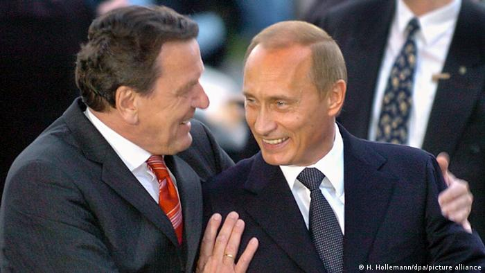 Former German Chancellor Gerhard Schröder talking to Russian President Putin
