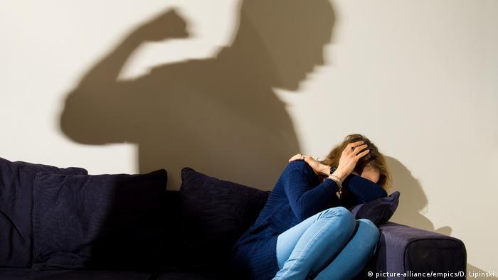 Женщина закрывает лицо и голову руками от мужчины, который замахнулся на нее