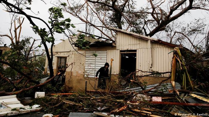 Homem busca itens de valor em casa danificada de um parente na área de Guayama. (Reuters/C.G. Rawlins)