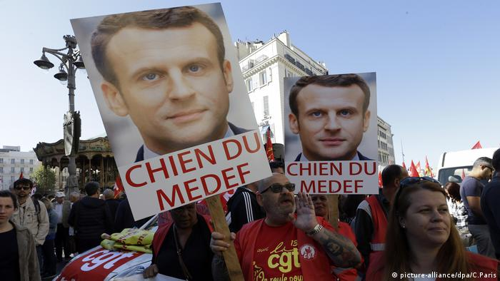 Protesters holding posters calling Macron the lapdog of an employer's group (picture-alliance/dpa/C.Paris)