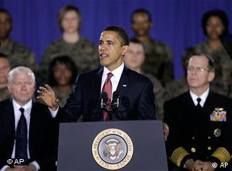 President Barack Obama speaks during a visit to Camp Lejeune, N.C., Friday, Feb. 27, 2009 as Defense Secretary Robert Gates, left, and Chairman of the Joint Chiefs Chairman Adm. Michael Mullen listen.. (AP Photo/Gerry Broome)