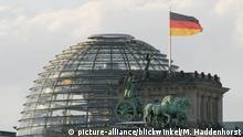 الجزء الأعلى من بوابة براندنبورغ التاريخية وخلفها القبة الزجاجية للبرلمان الألماني (بوندستاغ)