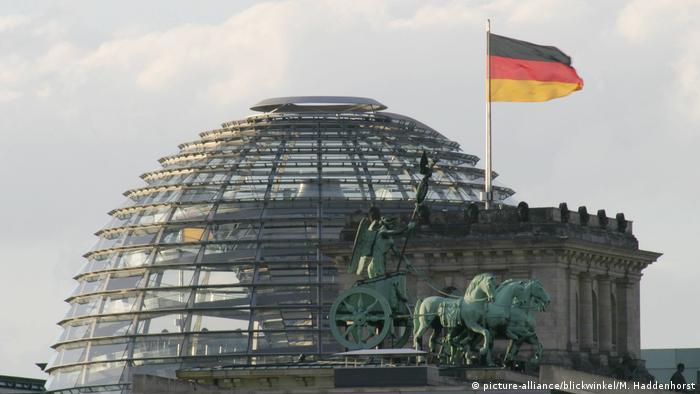 Viergespann auf dem Brandenburger Tor vor der Kuppel des Reichstags