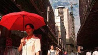 With a red umbrella shielding her from a hot afternoon sun, a woman strolls through the streets of Shenzhen's old district April 7, 1998. In back is one of the new high-rise buildings that symbolizes a new China. (AP Photo/Vincent Yu