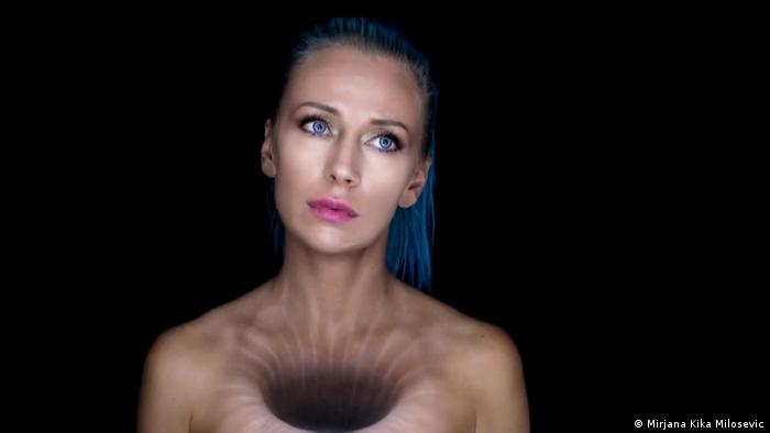 body painter Mirjana Milosevic against a black background seemingly with a hole in her chest (Mirjana Kika Milosevic)