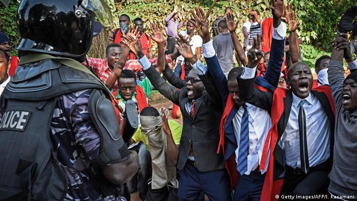 Students at Makere University in Uganda protesting as police officers look on (Getty Images/AFP/I. Kasamani)