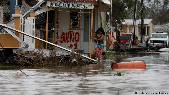 A woman walks out from her house after Hurricane Maria in Salinas, Puerto Rico, September 21, 2017